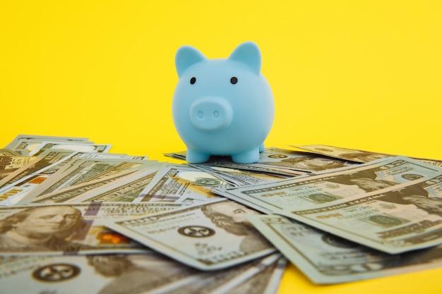 Blaue sparschwein-sparbüchse im stapel von dollar-banknoten auf gelb