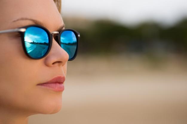 Blaue spiegelsonnenbrille sexy frauschönheit am strand. reiseurlaubskonzept.