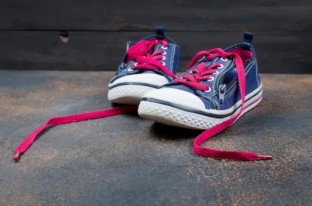 Blaue sportschuhe mit rosa schnürsenkeln auf dem boden