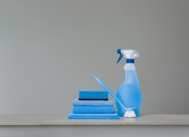 Blaue sprühflasche mit kunststoffspender, schwamm, scheuerbürste für teller und tuch für staub auf grau reinigen