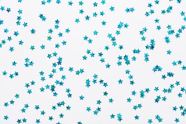 Blaue sterne glitzern konfetti auf weißem hintergrund