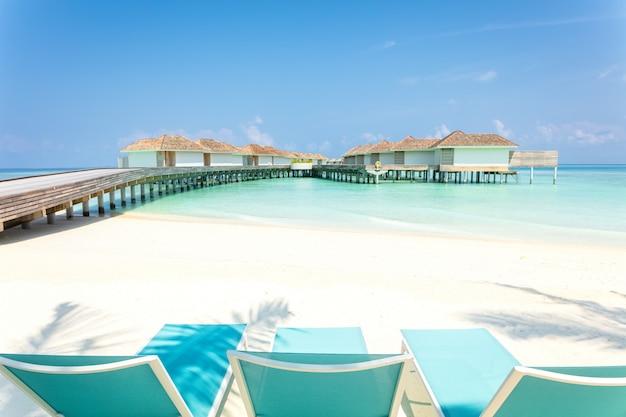 Blaue strandstühle auf weißem sand mit hölzerner anlegestelle und tropischen landhäusern in malediven am hintergrund, tropischer feiertag.