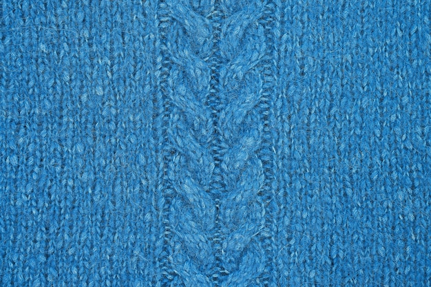 Blaue strickstruktur mit einem reliefmuster in der mitte. handgemachte strickwaren.