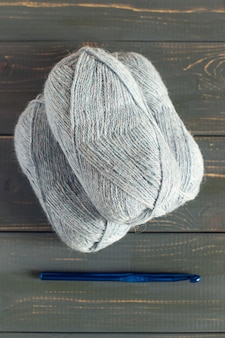 Blaue strickwolle und stricknadeln.
