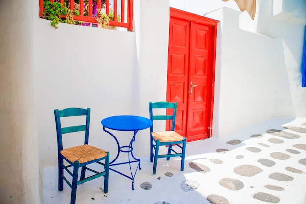 Blaue stühle und tabelle auf straße des typischen griechischen traditionellen dorfs mit weißen häusern auf mykonos-insel, griechenland, europa