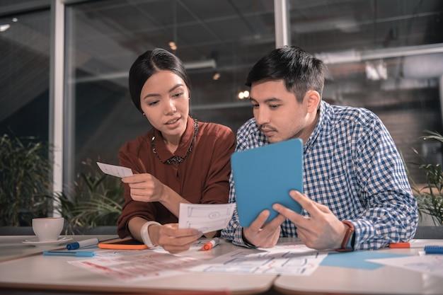 Blaue tablette. moderne intelligente freiberufler, die blaues tablett halten, während sie in nettem hub zusammenarbeiten
