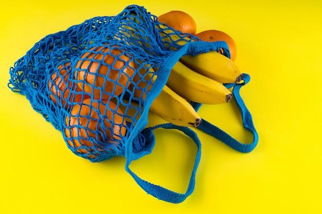 Blaue tasche mit bananen, roten äpfeln und mandarinen