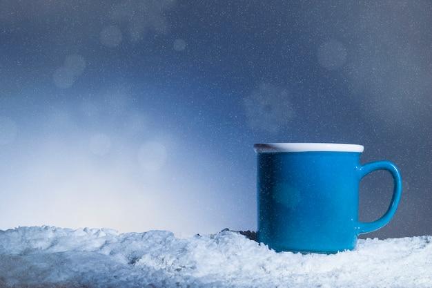 Blaue tasse auf schnee gelegt