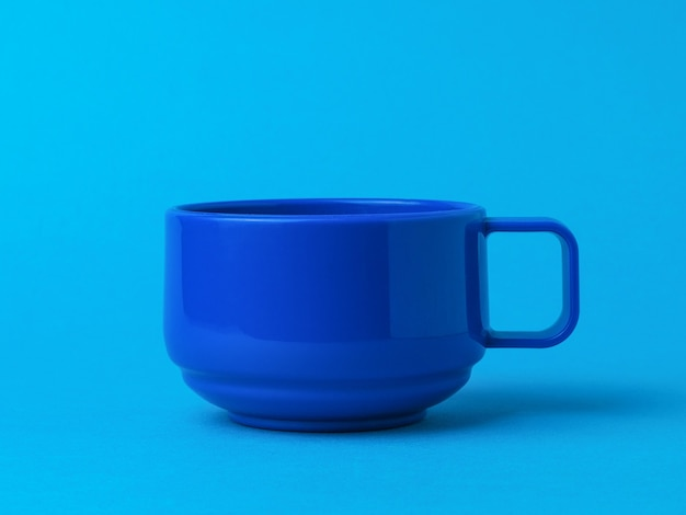 Blaue tasse für tee oder kaffee auf einem blauen hintergrund. der stil des minimalismus.