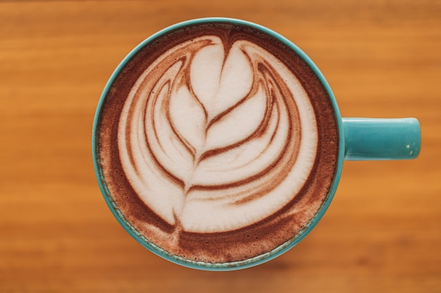 Blaue tasse kaffee mit voller latte art auf holztisch