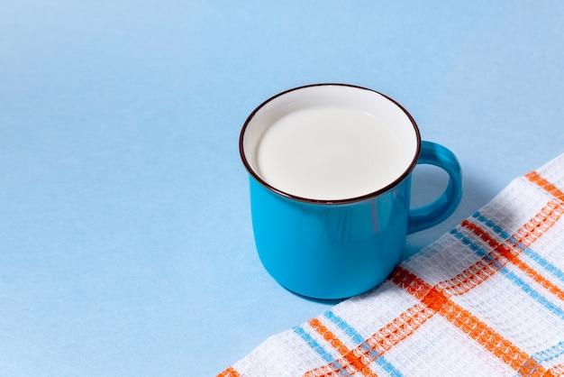 Blaue tasse milch und kariertes handtuch