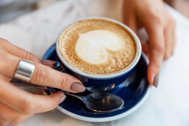 Blaue tasse mit cappuccino mit herzförmigem schaum in weiblichen händen an einem tisch in einem café. nahansicht. weicher fokus.