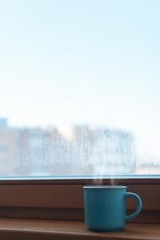 Blaue tasse mit heißem getränk, die morgens auf der fensterbank am fenster im zimmer steht. platz kopieren. konzept eines belebenden getränks, guten morgen. vertikales foto