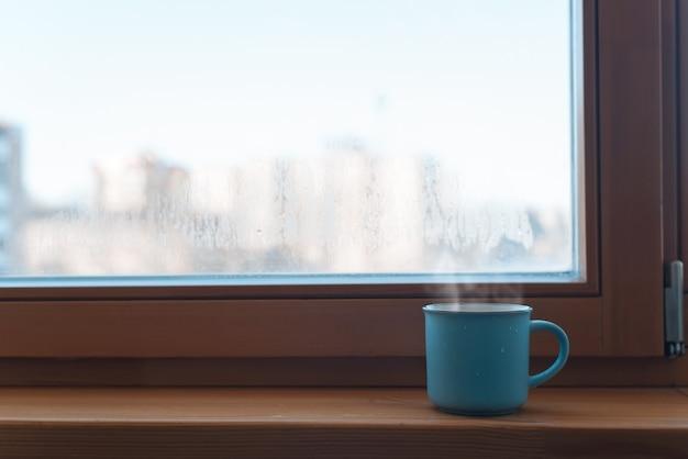Blaue tasse mit heißem getränk, die morgens auf der fensterbank am fenster im zimmer steht. platz kopieren. konzept eines belebenden getränks, guten morgen.