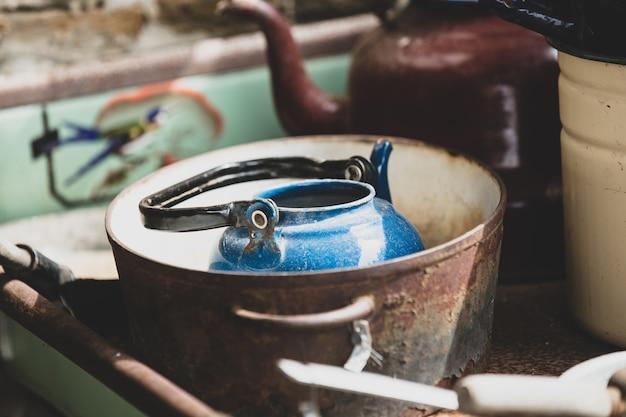 Blaue teekanne im rostigen topf.