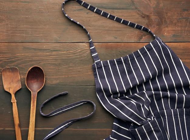 Blaue textilküchenschürze mit weißen streifen und holzlöffeln, draufsicht