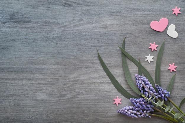Blaue traubenhyazinthenblüten auf dunkelgrauem holz, flach liegend mit