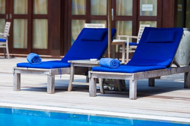 Blaue tücher auf ruhesesseln nähern sich swimmingpool am tropischen erholungsort