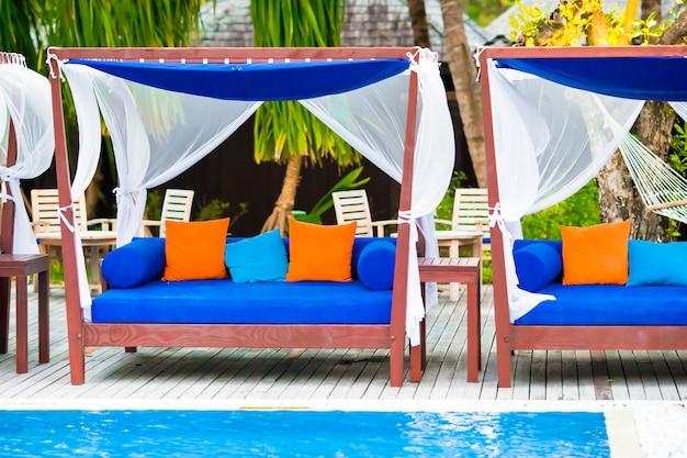 Blaue tücher auf strandbetten nähern sich swimmingpool am tropischen erholungsort