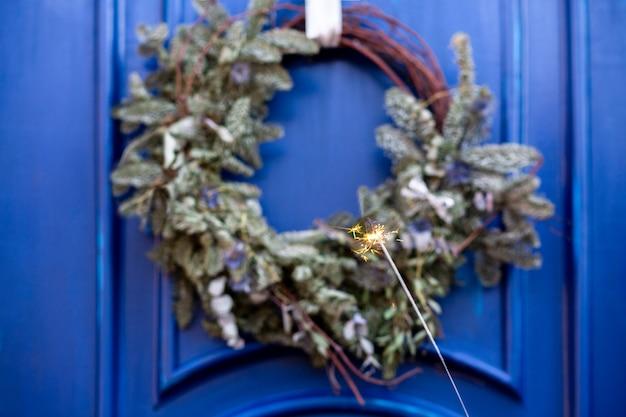 Blaue tür mit weihnachtskranz und wunderkerze.