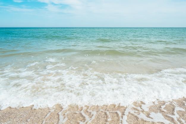 Blaue türkisfarbene meereswellen mit sand- und himmelswolken