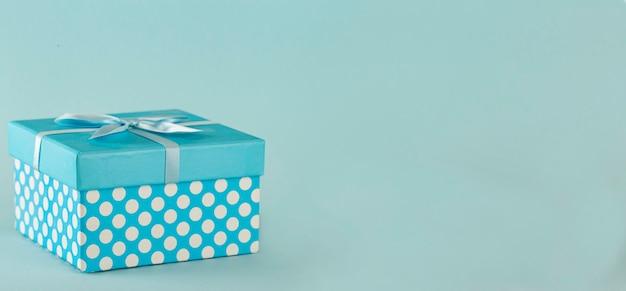 Blaue tupfen-geschenkbox mit schleife auf blauem hintergrund kopieren sie den raum