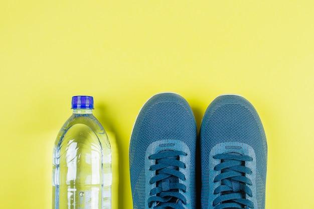 Blaue turnschuhe, trinkflasche. gelber hintergrund konzept des gesunden lebensstils