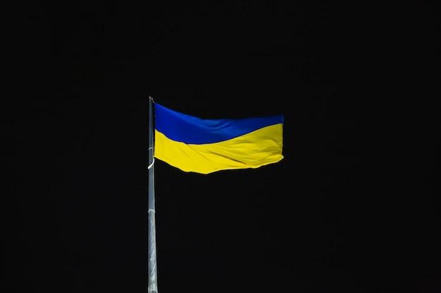 Blaue und gelbe flagge der ukraine, die im wind gegen den nachthimmel flattert nationales ukrainisches symbol