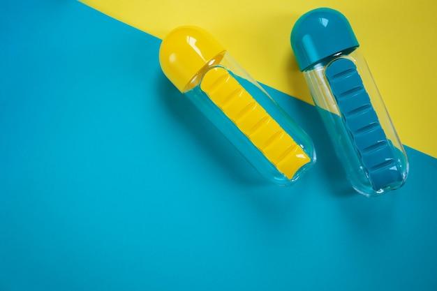 Blaue und gelbe wasserflaschen auf blauem und gelbem hintergrund