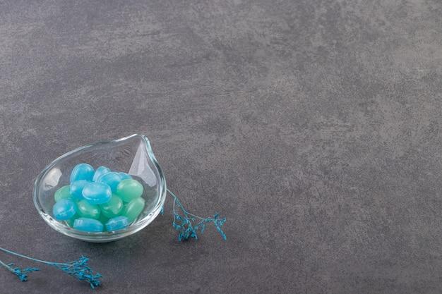 Blaue und grüne bonbons in der schüssel auf steintisch gelegt.