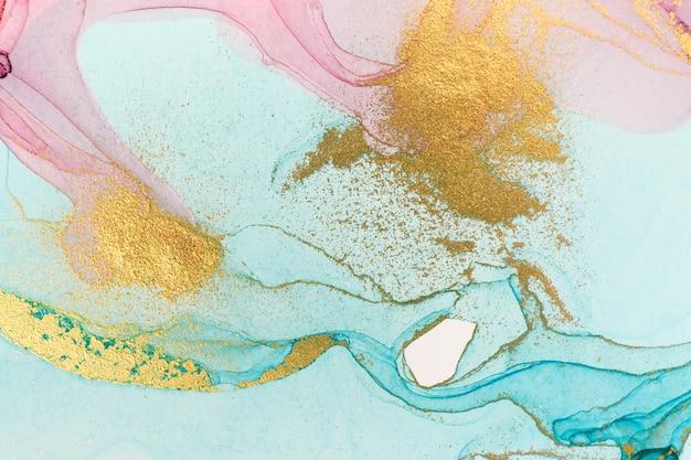 Blaue und rosa abstrakte tropfen mit goldpartikeln
