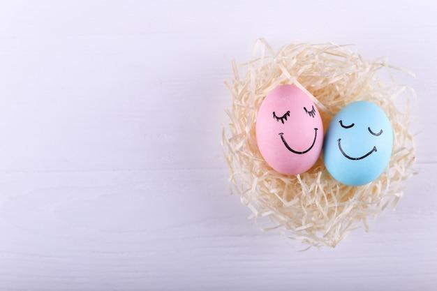 Blaue und rosafarbene eier mit gemaltem lächeln im nest, kopienraum. fröhliche ostern konzept grußkarte design.