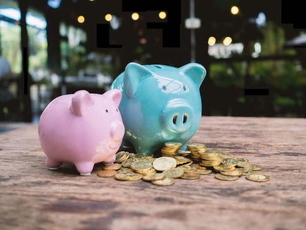 Blaue und rosafarbene zwei sparschweine mit goldmünzenstapel, geld sparen für zukünftige investitionspläne und pensionsfondskonzept.