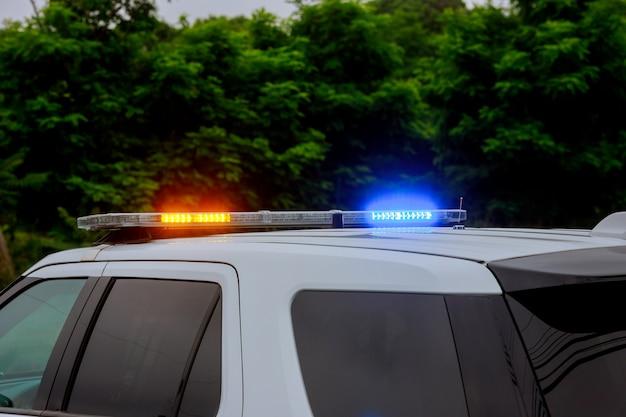 Blaue und rote blinkende sirenen des polizeiauto während der straßensperre