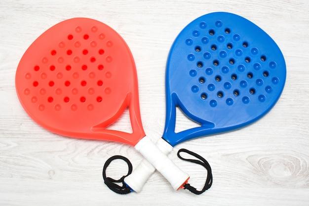 Blaue und rote paddle-tennisschläger auf weißem holztisch draufsicht
