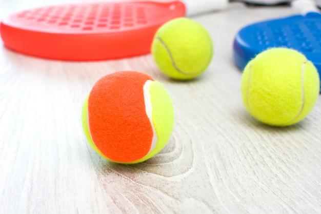 Blaue und rote paddle-tennisschläger und bälle auf weißem holztisch