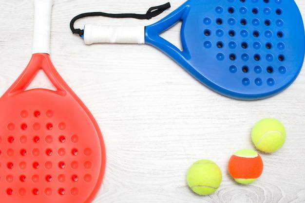 Blaue und rote paddle-tennisschläger und ball auf weißem holztisch draufsicht