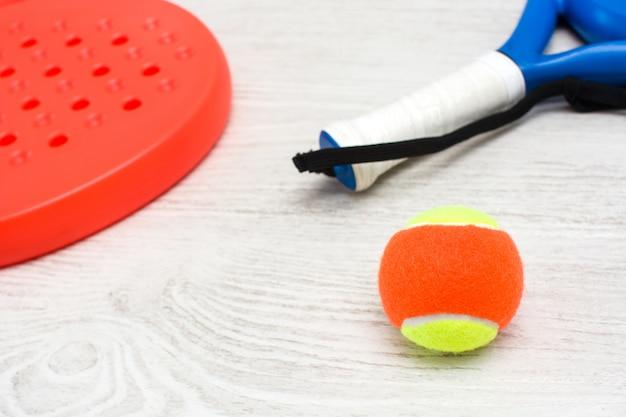 Blaue und rote paddle-tennisschläger und ball auf weißem holztisch