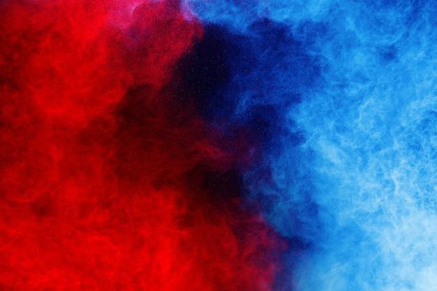 Blaue und rote pulverexplosion auf schwarzem hintergrund