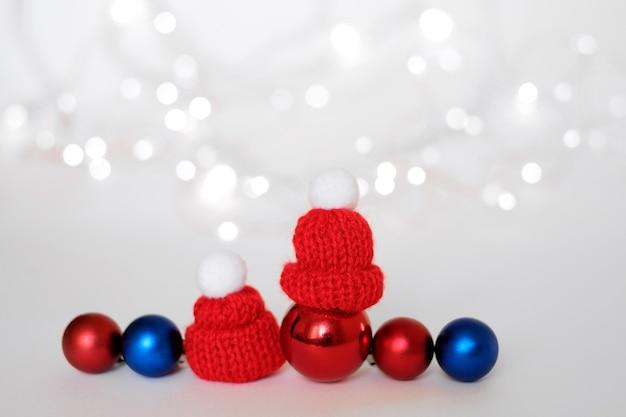 Blaue und rote weihnachtskugeln, die eine warme strickmütze tragen