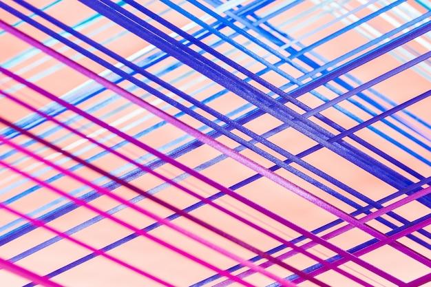 Blaue und violette textillinien auf rosa hintergrund. kreatives detail des innenraums des raumes