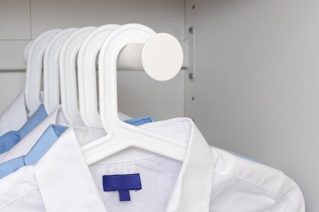 Blaue und weiße klassische hemden auf kleiderbügeln in einer garderobe