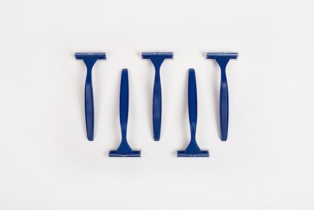Blaue unisex-rasierer auf weißem hintergrund minimaler stil flach draufsicht