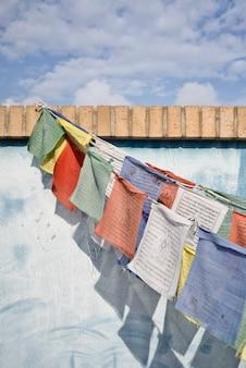 Blaue wand mit tibetischen gebetsfahnen