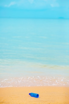 Blaue wasserflasche am strand mit dem hintergrund des blauen meeres