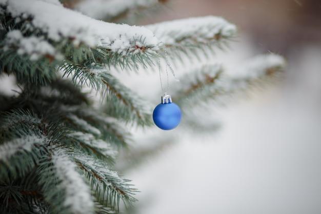 Blaue weihnachtsbaumkugeln. spielzeug auf schneebedeckten weihnachtsbaum. weihnachtshintergrund. erster schneefall.