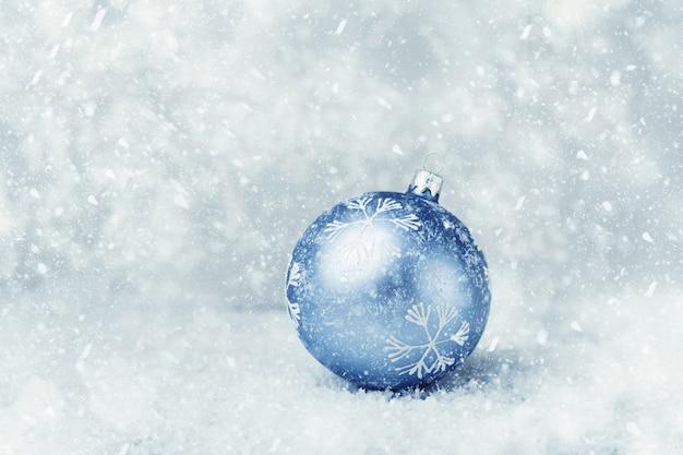 Blaue weihnachtskugel auf dem schnee