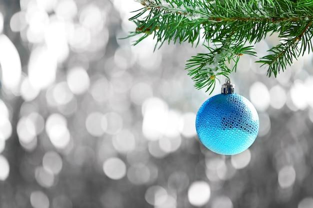 Blaue weihnachtskugel auf tannenzweig und glitzeroberfläche