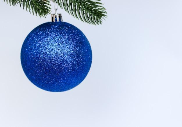 Blaue weihnachtskugeldekoration, die auf tannenzweig hängt