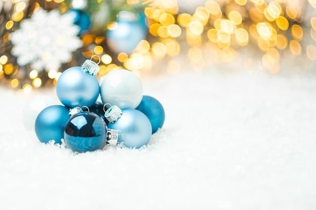Blaue weihnachtskugeln, die auf dem schnee auf dem hintergrund des weihnachtsbaumes liegen